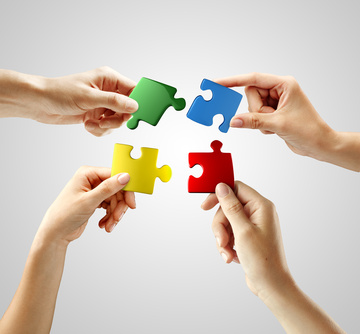 Hands and puzzle on gray background. Teamwork solving a puzzle
